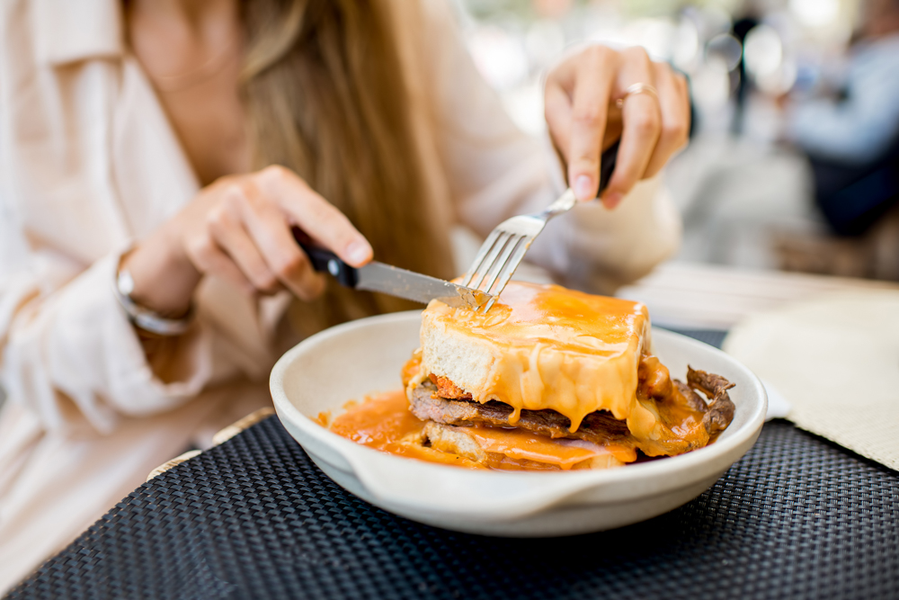 Woman cuts a very cheesy sandwich with a knife and fork in a cafe.