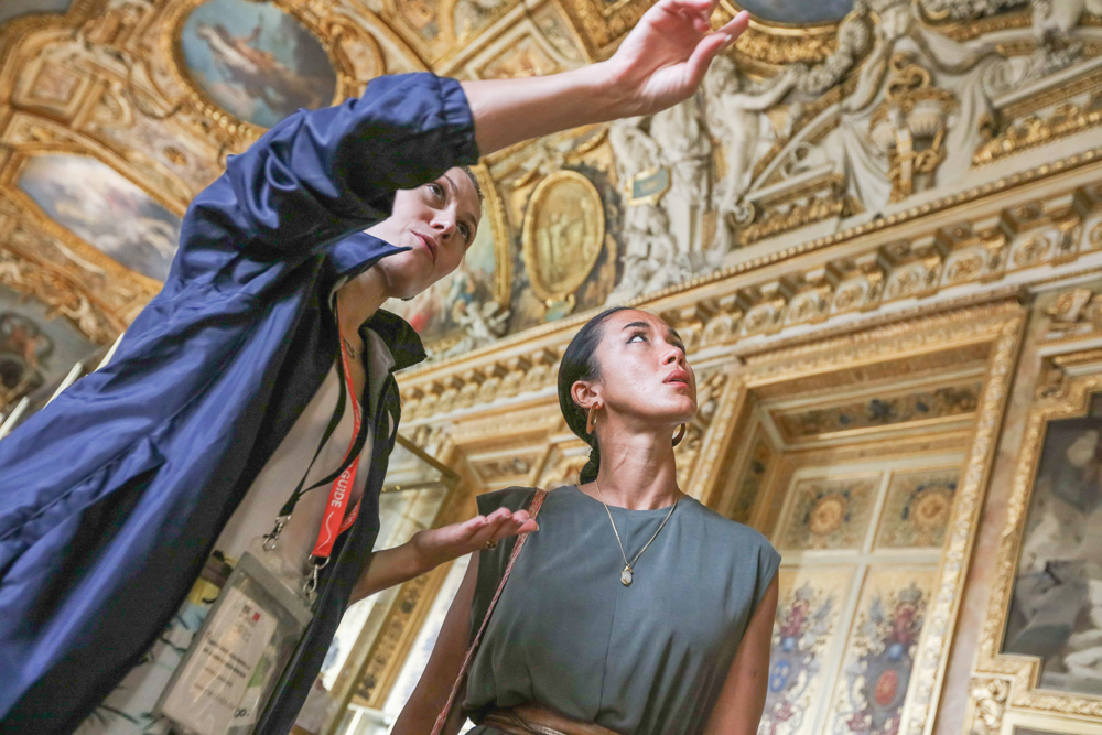 Female guide shows a young woman around Versailles explaining its history.