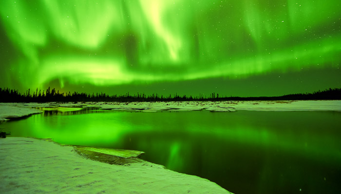 Northern Lights in bright green tone reflection on lake surrounded by snow.