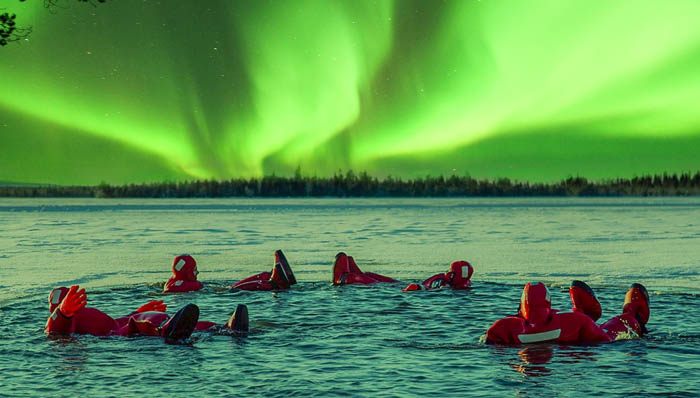 Four people floating on a lake looking up at the sky and watching the Northern Lights. That's what we call a real immersive aurora experience.