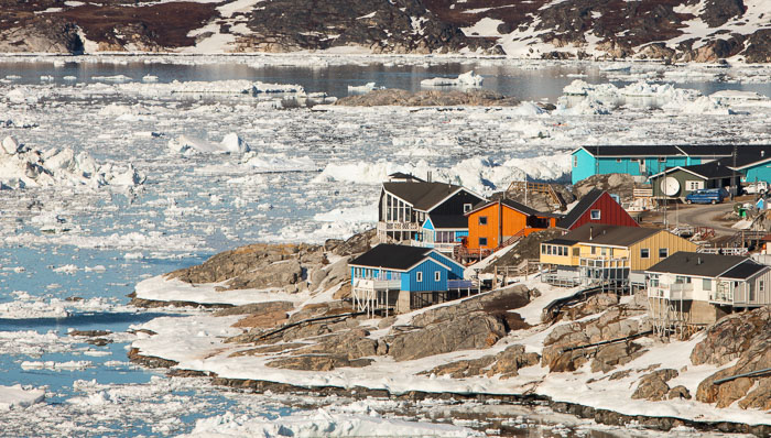 Houses on the partly frozen shore. Greenland is an excellent destination for those looking for an off the beaten track aurora experience.