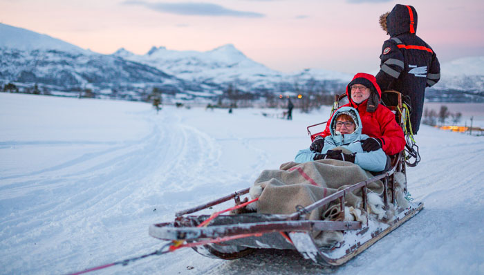 Senior couple dogsledding for a real Nordic experience in winter. Outside the cities, riding a dogsled pulled by huskies is an exciting way to start aurora chasing experience.