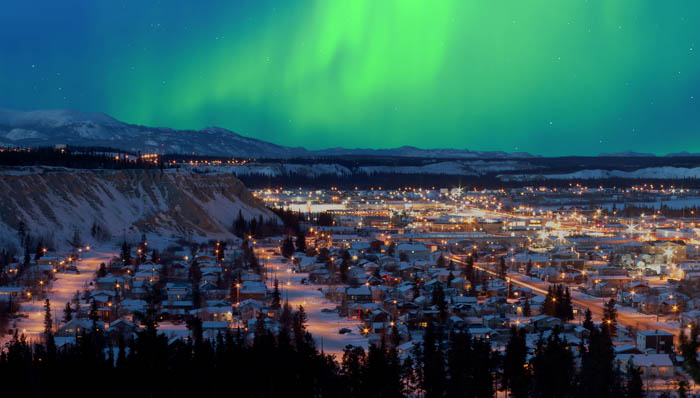 Lit town surrounded by snowy hills seen from above at night. Updated definition of thrill: gazing at the Northern Lights from your hotel room.