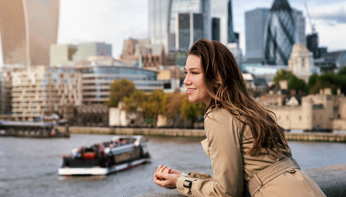 Tourist woman in a trench coat enjoys the view over the Thames river to the skyline of London, United Kingdom
