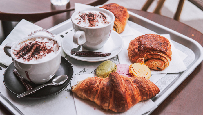 Pain chocolate, French croissant, and artisan cappuccinos. French breakfast in a cafe.