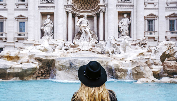 Blonde woman with a black hat looks out at the Trevi Fountain in Rome, Italy.
