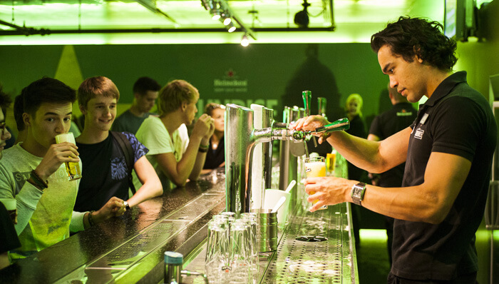 Young man pours a beer for a group of young men at the Heineken experience in Amsterdam.