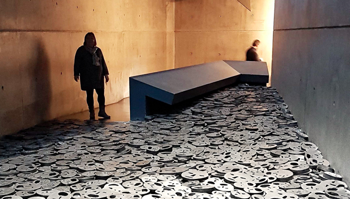 Photo inside the Jewish Museum of thousands of steel faces on the ground.