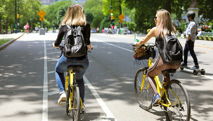 Two young women with backpacks bike around Central Park in New York City