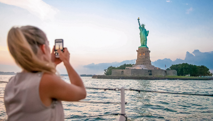 Young woman with a ponytail takes a picture of the Statue of Liberty while on a boat sailing by.