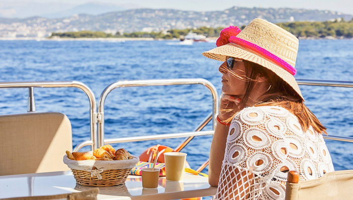 A woman with an holiday hat and sunglasses is enjoying breakfast with croissant and café on a boat cruise