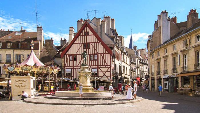 Place in Dijon with a fountain, a statue in the middle and a carousel, typical Burgundy house in the background