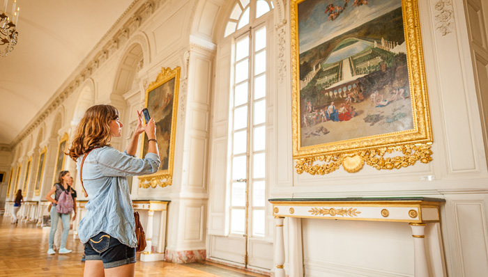 A young women taking picture of a painting in the gallery of Palace of Versailles