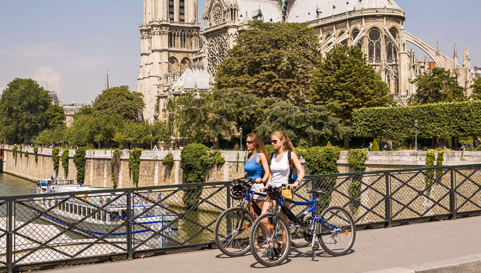 Two women with bikes walking at l'ile de la Cité near Notre Dame de Paris with a bateau mouche in the background