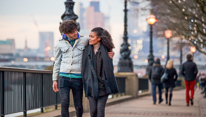 Young couple walk along the River Thames in London in Autumn. Man has his arm around the woman.