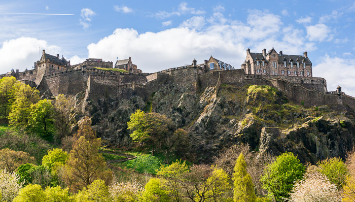 Beautiful greenery surrounds the Edinburgh Castle on a sunny day with blue skies