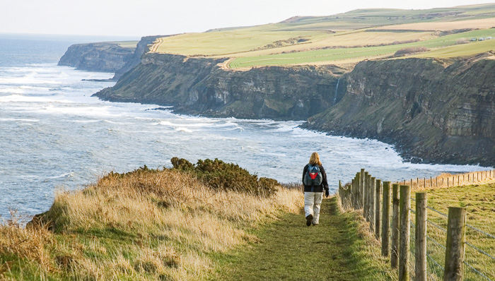 Woman backpacks across the countryside somewhere in the UK next to a cliff facing coast.
