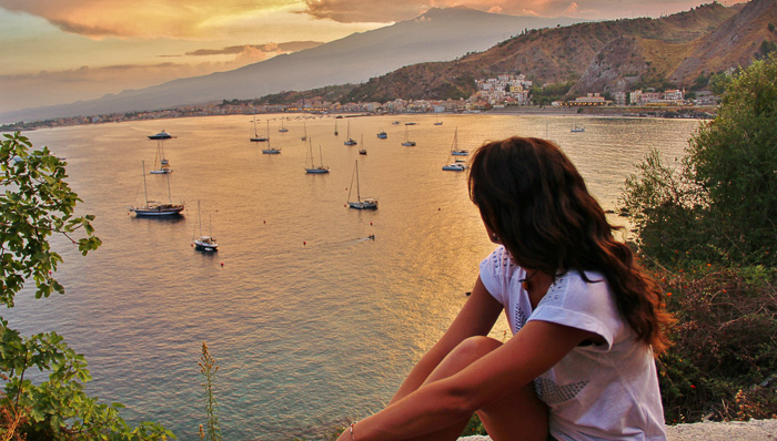 Young woman with dark brown hair looks out over the water as the sun sets over sailboats.