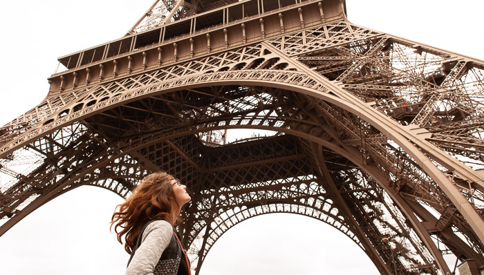 Young woman looks up at the Eiffel Tower while standing directly below in Paris