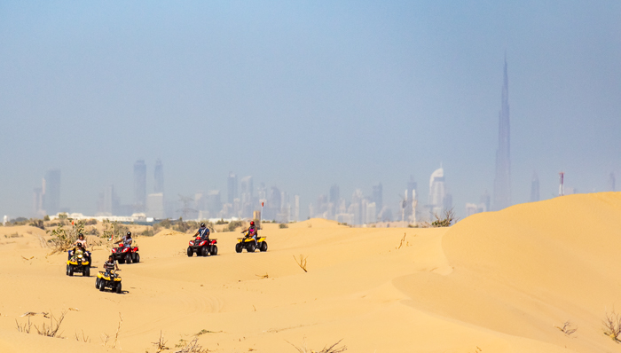 People drive on 4-wheelers in the Dubai Desert with the Burj Khalifa in the background.