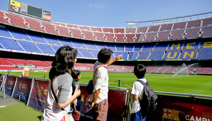 A young family looks out onto the field of Camp Nou, the stadium home to FC Barcelona in Spain