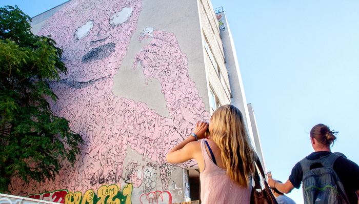 Young woman takes a picture of large street art in Berlin