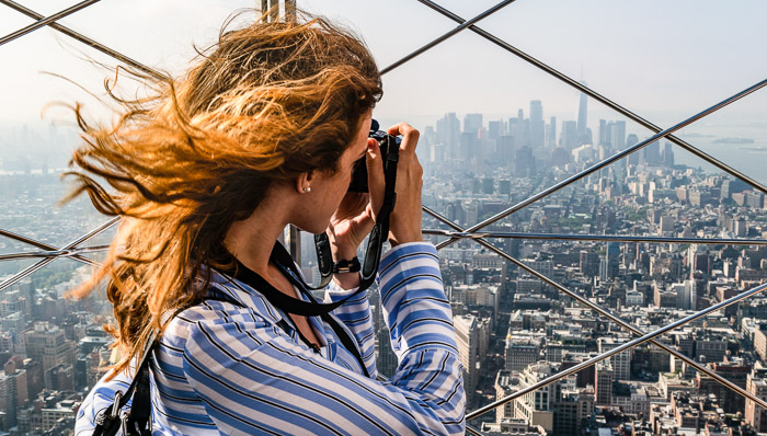 Young woman takes a photo of the New York City skyline from atop the Empire State Building.