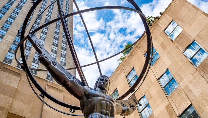 View of a statue of a strong man holding up a globe in New York City on a sunny day.