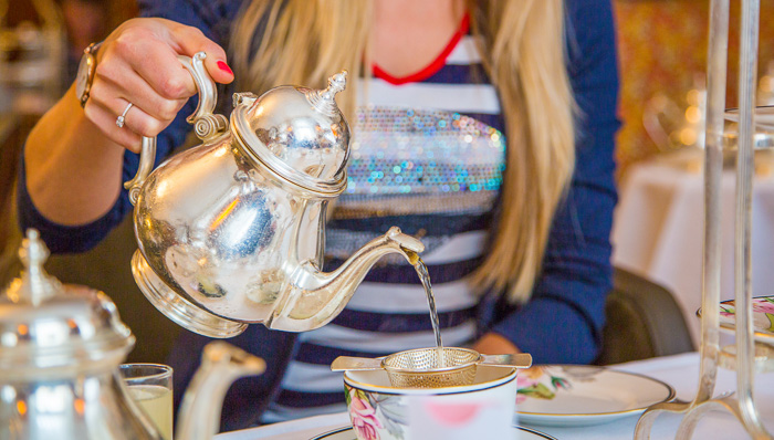 Young blonde woman in sparkly striped top pours tea from a classic silver teapot into her teacup in London