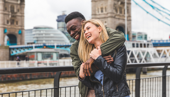 Young couple embrace, smiling and laughing next to the River Thames in London