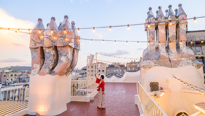 Woman in traditional clothing takes a picture of the skyline from a rooftop, surrounded by large silver columns.