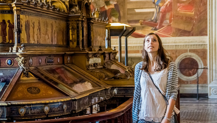 Young woman in a white top with striped cardigan wanders a Catholic church in Rome.