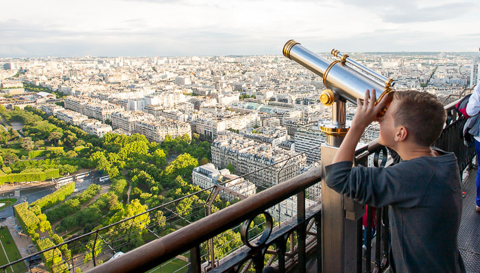 Boy looks through coin binoculars overlooking one of the promenades of Paris, France