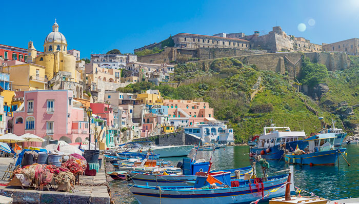 Colorful shot of of a town in Italy with pink, blue, and yellow buildings on the blue water with small fishing boats.