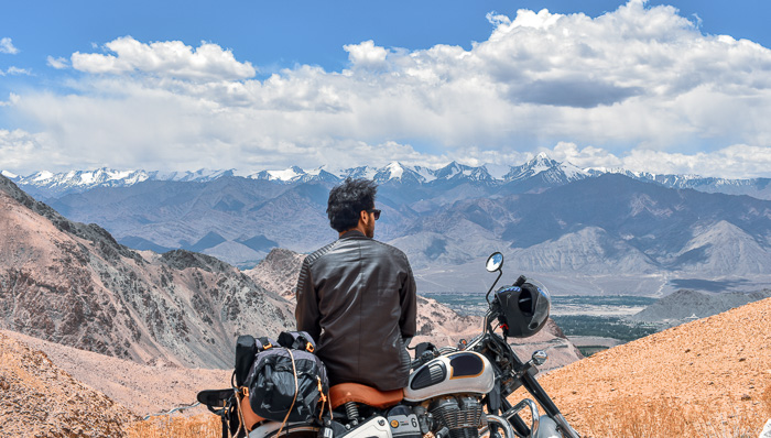 Young, dark-haired motorcyclist wearing sun glasses sits on his motorcycle with a leather jacket looking out over the mountains and blue skies.