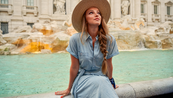 Young blonde woman sits on the Trevi Fountain with a hat and blue dress.