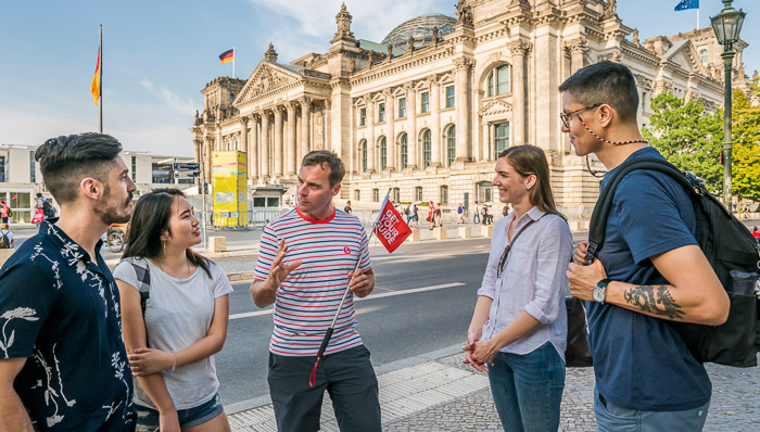 GetYourGuide host in striped shirt holds flag and gudies tourists on walking tour of Berlin, Germany