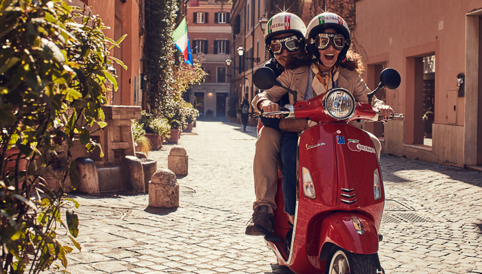 Young couple rides a red Vespa in Italy with helmets and goggles and an Italian flag in the background.