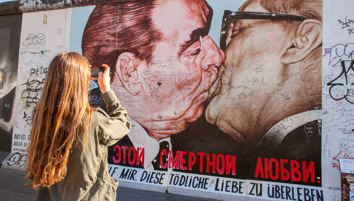 Young woman takes a photo of the famous East Side Gallery portrait of politicians kissing