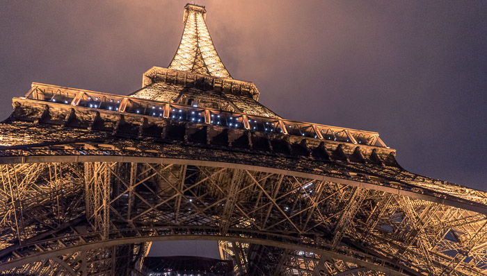 Shot from below of the Eiffel Tower in Paris lit up at night