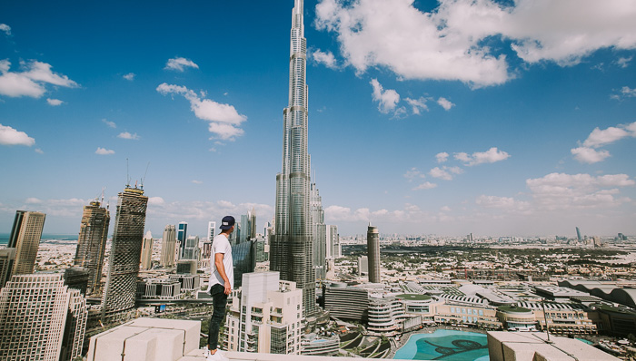 Man standing on top of a building overlooking Burj Khalifa, tallest building in the world, and the Dubai skyline.