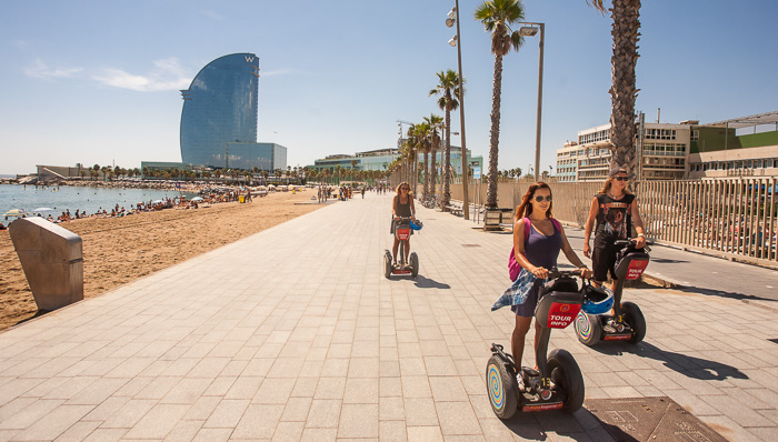 Women ride segways along the beaches in sunny Barcelona with palm trees in the background