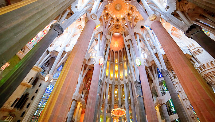 Interior view of the ceiling of La Sagrada Familia in Barcelona. Daytime with sunlight coming through stained glass windows