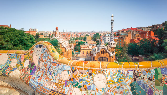 Orange mosaic wall from Gaudi in Park Güell against the backdrop of Barcelona and its colorful rooves