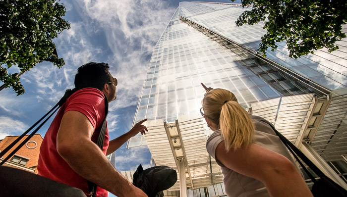 Couple look up at the London Shard and point. The building is silver and glass and it is sunny and warm