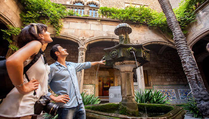 Man and woman look up at the architecture of Barcelona while standing next to a small fountain in a court yard