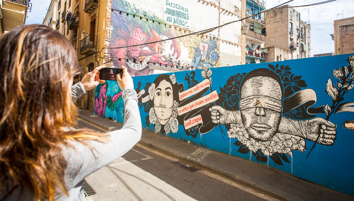 Woman takes a picture of a graffiti wall in central Barcelona. The wall is blue with political statements and cartoon figures.