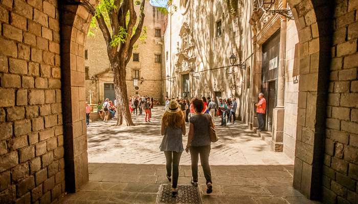 Two women walk through the sunny, tree-lined streets of Barcelona.