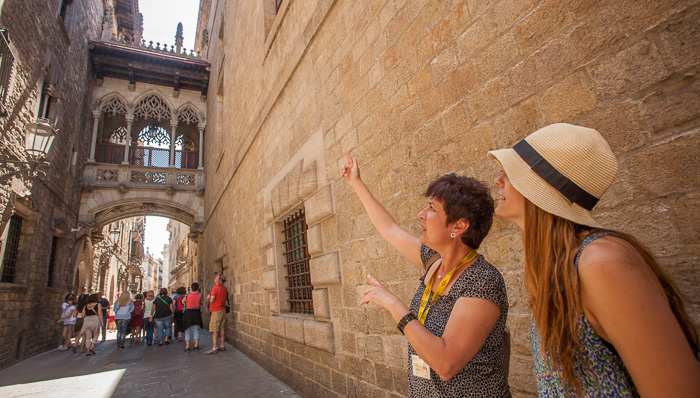Tour guide and tourist walk the streets of Barcelona. The tour guide is pointing up at the architecture and explaining something