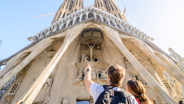 Man gestures up at La Sagrada Familia as he speaks to a woman. The couples stands at the entrance in the sun